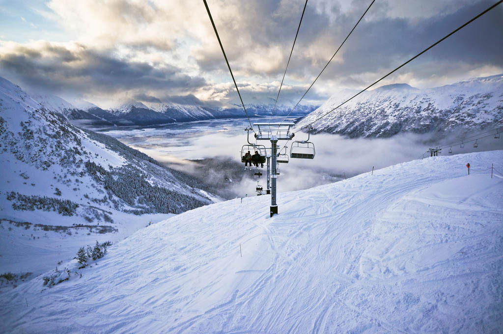 Skiers riding chairlift down mountain in Alyeska, Alaska