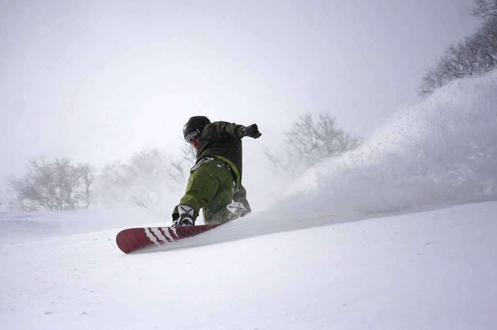 Man snowboarding down mountain in Niseko, Japan