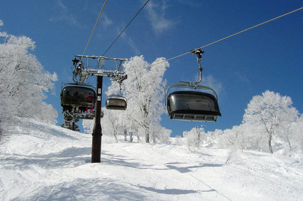 Skiers riding chairlift in Norzawa Onsen, Japan